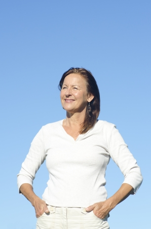 Portrait beautiful looking confident relaxed middle aged woman posing happy smiling sunny outdoor, isolated with blue sky as background and copy space. Stock Photo - 16885331