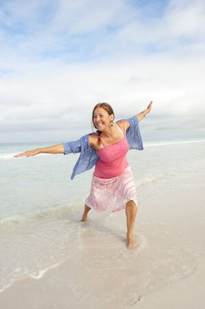 sexy mature women: Attractive middle aged woman happy and joyful with arms up in shallow water at beach, wearing pink and blue, isolated with ocean and sky as background and copy space.
