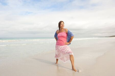 Attractive middle aged woman happy and confident with in shallow water at beach, wearing pink and blue, isolated with ocean and sky as background and copy space. Stock Photo - 16922055