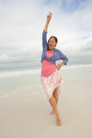 Pretty middle aged woman with arms up happy and confident at beach vacation enjoying active retirement, isolated with ocean and cloudy sky as background and copy space. photo