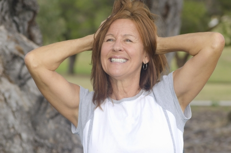 Portrait fit and healthy, confident and happy attractive middle aged woman with arms up, with blurred background outdoor.
