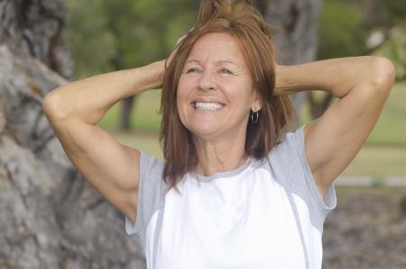 confianza: Retrato en forma y saludable, segura y feliz atractiva mujer de mediana edad con los brazos hacia arriba, con el fondo borroso al aire libre.