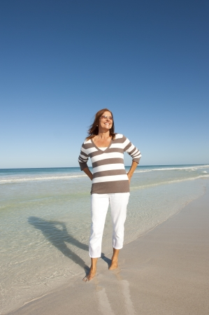 Portrait Active and attractive middle aged woman enjoying happy retirement with holiday at beach, isolated with ocean and sky as background and copy space. Stock Photo - 17181463