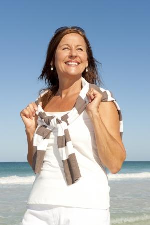 Ritratto attivo e attraente donna di mezza et� godendo la pensione felice vacanza in spiaggia, isolato con mare e cielo come sfondo e copia spazio.