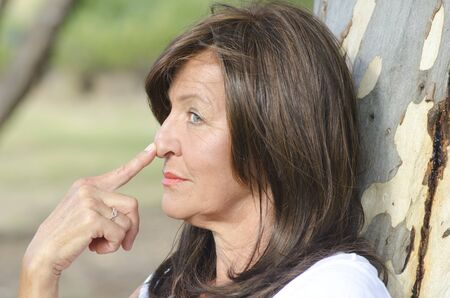finger tip: Portrait profile of attractive mature woman outdoor thoughtful in park with blurred background and copy space, with finger tip on nose. Stock Photo