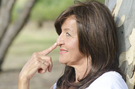 finger tip: Portrait profile of attractive mature woman outdoor in park with blurred background and copy space, with finger tip on nose. Stock Photo