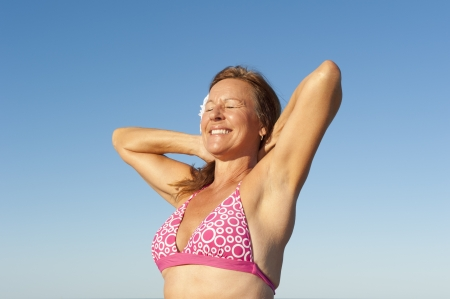 bathers: Ritratto donna matura attraente in bagnanti rosa in posa con le braccia in alto