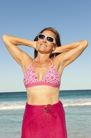 bathers: Ritratto attraente donna matura in bagnanti rosa e occhiali da sole in posa con le braccia fino Archivio Fotografico