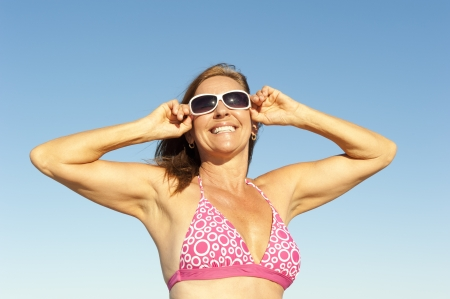 Portrait attractive mature woman in pink bathers and sunglasses posing with arms up photo