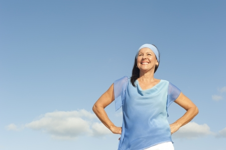 Portrait successful beautiful looking middle aged woman confident, happy and relaxed smiling, enjoying active retirement, isolated with blue sky as background and copy space. Stock Photo - 17382399