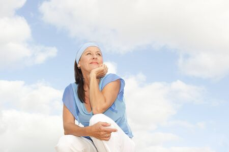 serenety: Portrait thoughtful relaxed attractive mature woman sitting outdoor contemplating, isolated with cloudy blue sky as background and copy space. Stock Photo