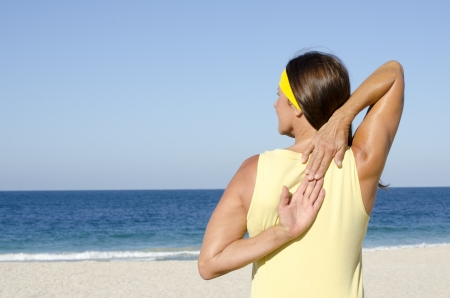 Portrait attractive fit and healthy mature woman relaxed stretch exercising at beach with finger touching on back, isolated with ocean and blue sky as background and copy space. Stock Photo - 17471022
