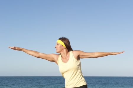 Portrait attractive fit and healthy mature woman relaxed exercising outdoor at beach with arms spread out balancing Stock Photo - 17471015