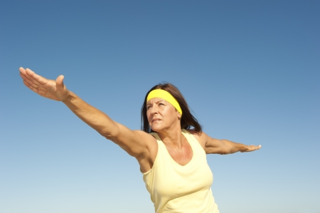active lifestyle: Portrait attractive fit and healthy mature woman relaxed exercising outdoor with arms spread out balancing, isolated with blue sky as background and copy space.
