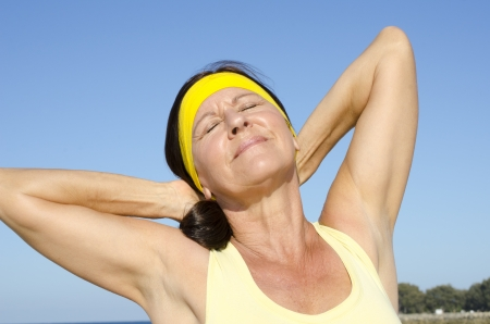 Portrait attractive and sporty fit mature woman relaxed with closed eyes and arms up enjoying sunny day outdoor photo