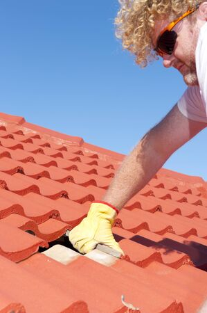 Roof repairs, worker with yellow gloves replacing red tiles or shingles on house with blue sky as background and copy space  Stock Photo - 17644122