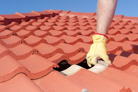 diy home repair: Roof repair, worker with yellow gloves replacing red tiles or shingles on house with blue sky as background and copy space