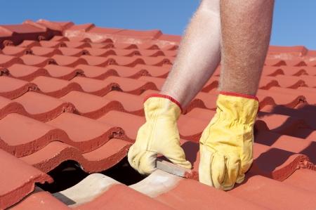 Tetto di riparazione, lavoratore con guanti gialli sostituzione tegole rosse o scandole in casa con il cielo azzurro come sfondo e lo spazio della copia