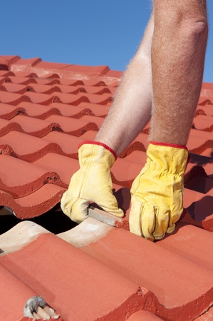 Roof repair, worker with yellow gloves replacing red tiles or shingles on house with blue sky as background and copy space Stock Photo - 17644124