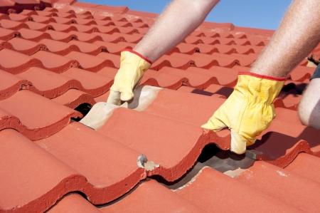 Riparazioni del tetto, operaio con i guanti gialli sostituzione tegole rosse o scandole in casa con il cielo azzurro come sfondo e lo spazio della copia