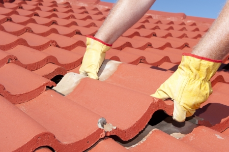Roof repairs, worker with yellow gloves replacing red tiles or shingles on house with blue sky as background and copy space.