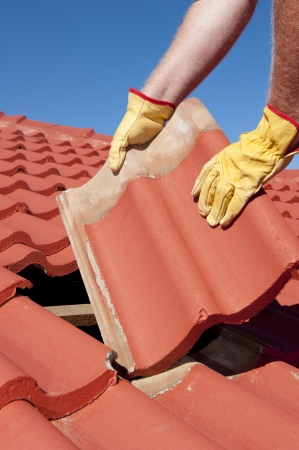 replacing: Roof repair, worker with yellow gloves replacing red tiles or shingles on house with blue sky as background and copy space. Stock Photo