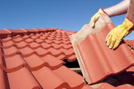 Reparaciones del techo, trabajador con guantes amarillos reemplazando tejas rojas o culebrilla en casa con el cielo azul como fondo y espacio de la copia.