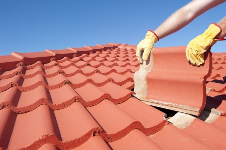 Roof repair, worker with yellow gloves replacing red tiles or shingles on house with blue sky as background and copy space. Standard-Bild