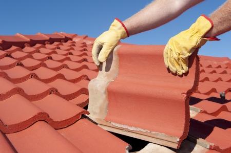 Riparazioni del tetto, operaio con i guanti gialli sostituzione tegole rosse o scandole in casa con il cielo azzurro come sfondo e lo spazio della copia.