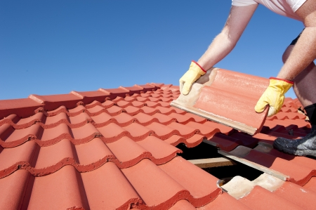 shingles: Reparación de techos, trabajador con guantes amarillos reemplazando tejas rojas o culebrilla en casa con el cielo azul como fondo y espacio de la copia.