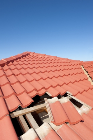 damaged roof: Damaged roof construction on house needs tiles or shingles repaired and replaced, red tiles and blue sky as background and copy space.