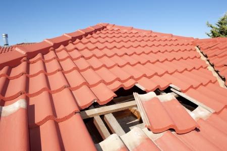 Costruzione tetto danneggiato sulla casa ha bisogno di piastrelle o tegole riparati e sostituiti, piastrelle rosse e blu cielo come sfondo e copia spazio.