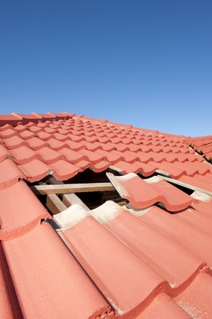 Damaged roof construction on house needs tiles or shingles repaired and replaced, red tiles and blue sky as background and copy space. Stock Photo - 17644201