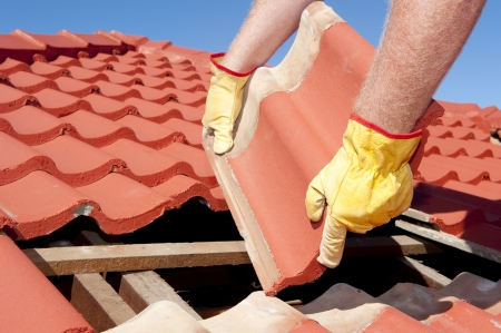 roofing: Roof repairs, worker with yellow gloves replacing red tiles or shingles on house with blue sky as background and copy space.