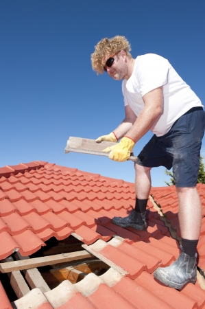 Roof repair, worker with yellow gloves replacing red tiles or shingles on house with blue sky as background and copy space. Stock Photo - 17644246
