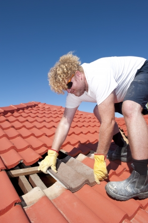 Roof repairs, worker with yellow gloves replacing red tiles or shingles on house with blue sky as background and copy space. Stock Photo - 17644251