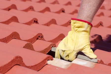 Roof repair, worker with yellow gloves replacing red tiles or shingles on house with tiles as blurred background and copy space. photo