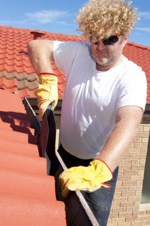 Handyman, worker cleaning gutter on house with shovel, roof with red tiles and shingles and blue sky as background. photo