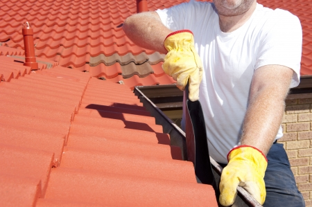 home repairs: Handyman, worker cleaning gutter on house with shovel, roof with red tiles and shingles  as background.