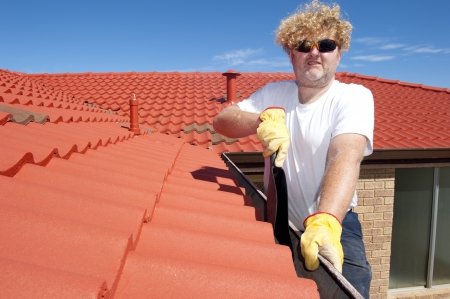 gutter: Handyman, worker cleaning gutter on house with shovel, roof with red tiles and shingles and blue sky as background copy space.. Stock Photo