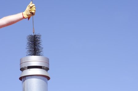 Arm with yellow glove holding sweeper to clean chimney on house, isolated with blue sky as background and copy space. Stock Photo