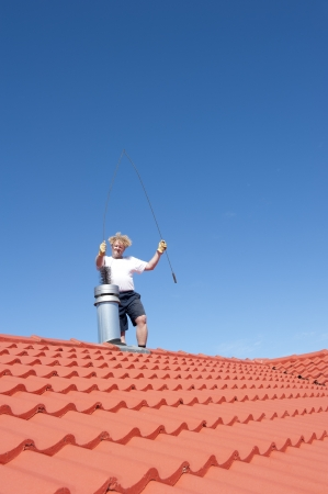 chimney sweep: Man standing on rooftop of residential building to clean metal chimney of house with sweeper, with blue sky as background and copy space.