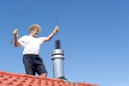 chimneys: Man standing on rooftop of residential building to clean metal chimney of house with sweeper, with blue sky as background and copy space.