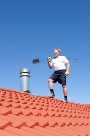 chimney sweep: Man standing on rooftop of residential building to clean metal chimney of house with sweeper, with red roof and blue sky as background and copy space. Stock Photo