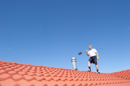 Man standing on rooftop of residential building to clean metal chimney of house with sweeper, with red roof and blue sky as background and copy space. Stock Photo