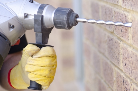 Closeup of hand with yellow glove holding drill at wall, with blurred background of house exterior