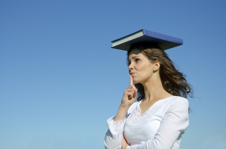 Young beautiful student girl with a big blue science book on the head isolated in front of blue sky with copy space photo