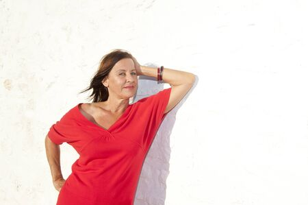 Portrait Sexy mature woman wearing red standing relaxed sunny day outdoor,  isolated on white wall background. photo