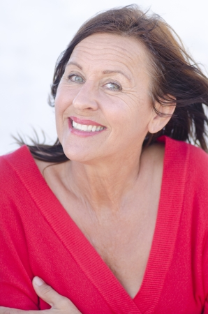 Portrait attractive retired middle aged brunette woman looking peaceful, relaxed and happy smiling, wearing red shirt, isolated on white background. Stock Photo