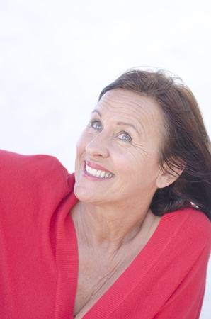 Portrait attractive retired middle aged brunette woman looking peaceful, relaxed and happy smiling, wearing red shirt, isolated on white background. photo